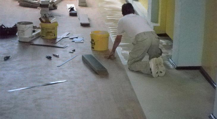 Applying glue for an Amtico school hall floor