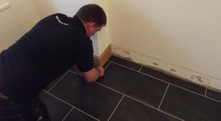 One of our vinyl flooring installers cutting in