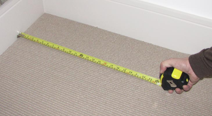 Measuring a Horsham floor with a tape measure