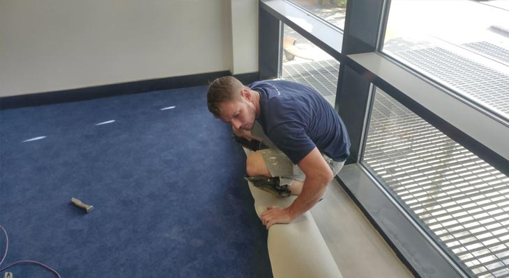 Library flooring expert dropping and trimming the carpet into the window