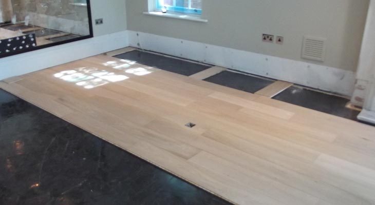 Installing wood flooring from the room middle outwards into either side of the fireplace
