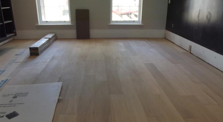 Skirting boards removed from engineered oak wood flooring allowing for expansion