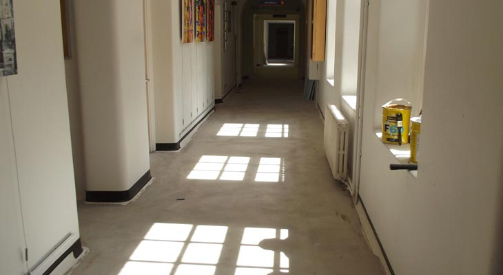 Capping strips installed along the walls of the college corridor