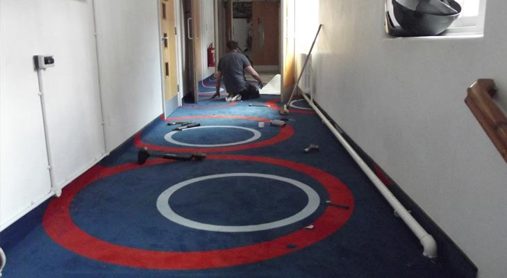 Euro-Pean Flooring commercial carpet specialist cutting around corridor heating pipes
