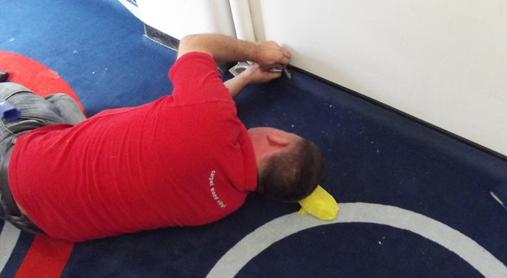 College flooring expert tucking carpet under the edging strip